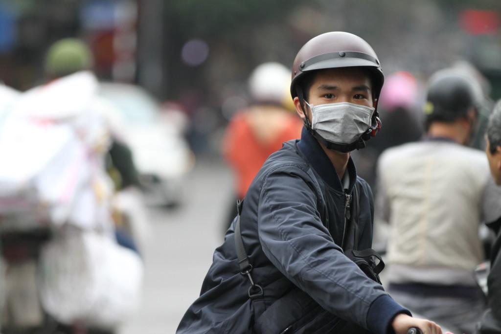 マスクをするバイク青年