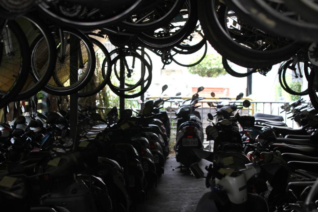 駅前の駐輪場は「超満員」。地面にバイクを駐車し、自転車は宙づりにされている
