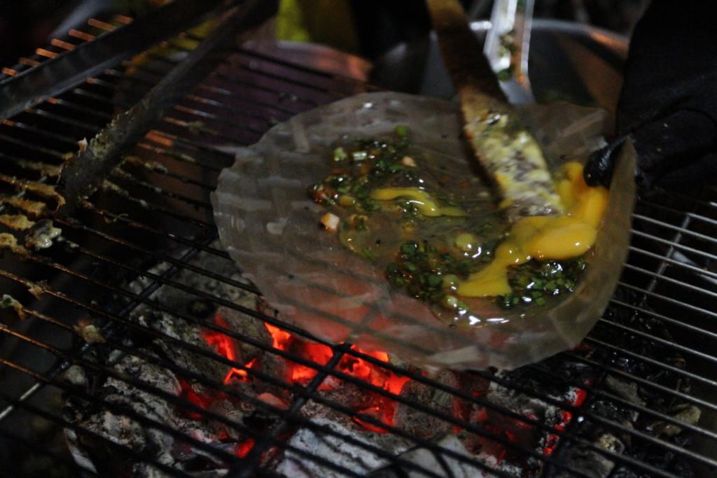 ライスペーパーを炭火にかけ、見事な手さばきで調理する