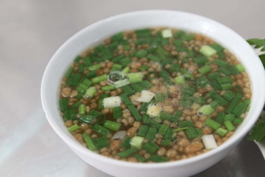 ネギと、小さな「おかき」のような粒が入ったスープ