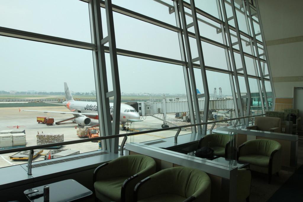 飛行機と滑走路の見える、ガラス張りの大きな窓