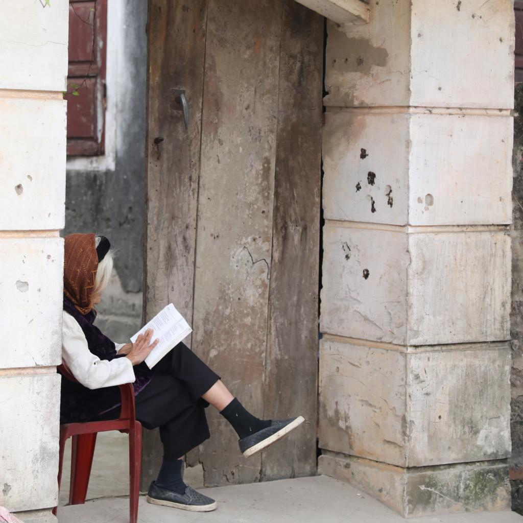 軒先で読書中のおばぁさん