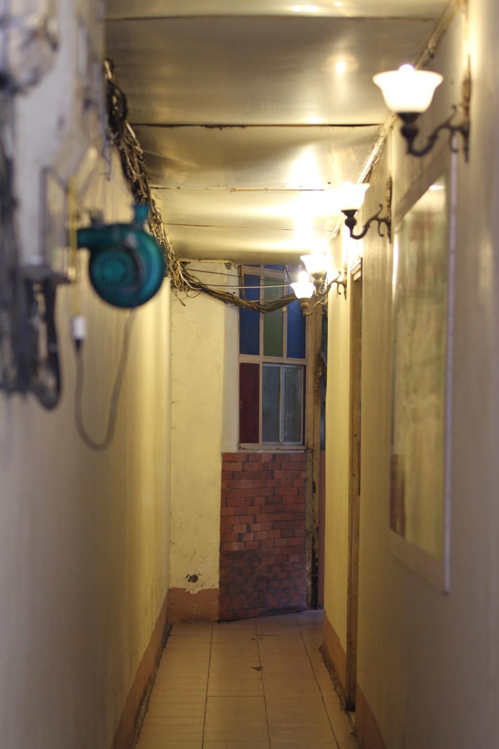 細長い廊下。店舗は階段を上ったところにある
